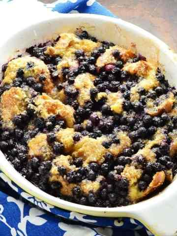 Blueberry french toast in white oval dish and blue-and-white cloth to left.
