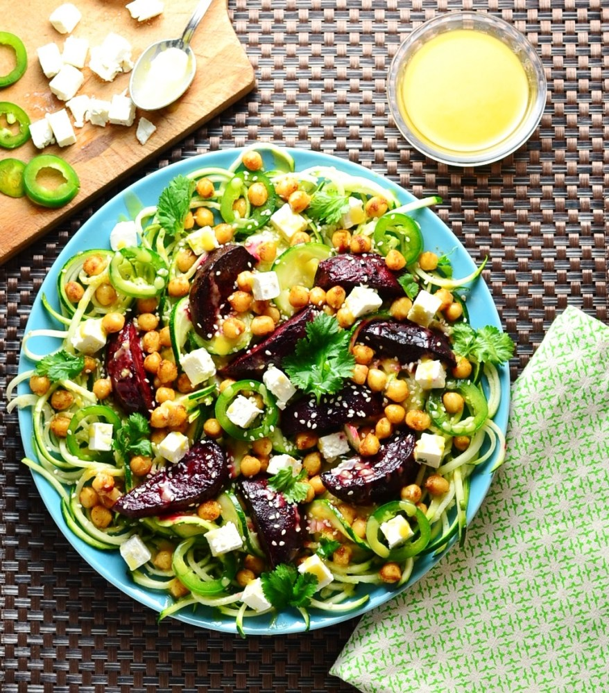 Top down view of beetroot chickpea zoodles salad with feta on top of blue plate, with yellow dressing in top right corner and cutting board with feta, green chillies and spoon in left.