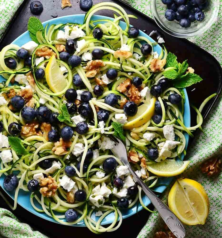 Top down view of blueberry feta salad with zoodles and lemon wedges on top of blue plate with fork, on oven tray, with green cloth in background.