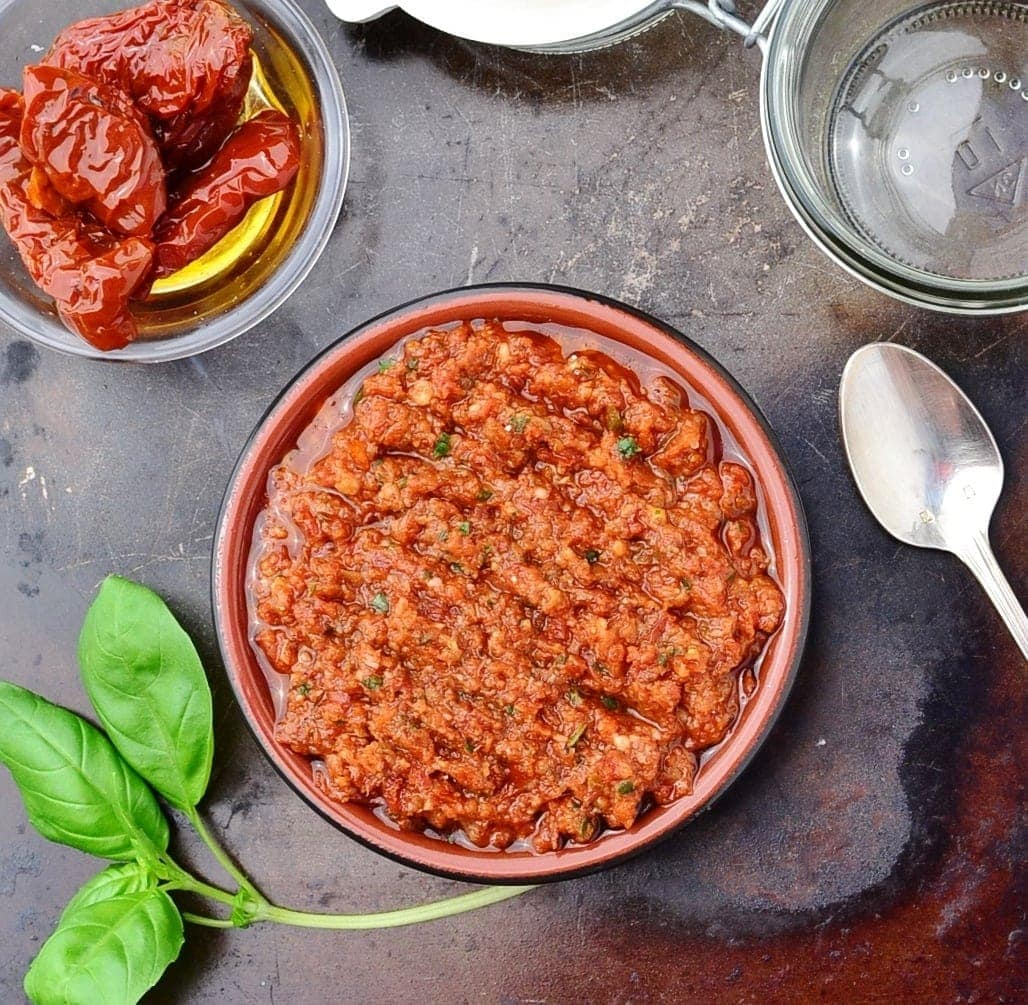 Top down view of sun dried tomato pesto sauce in round dish on top of dark surface with basil leaves, spoon, open jar and sun dried tomatoes in small dish.