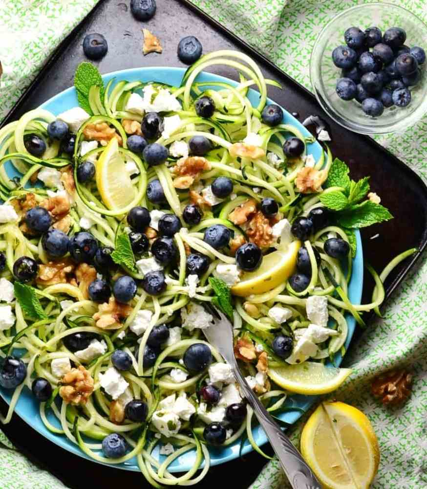Top down view of blueberry feta salad on top of zoodles, with lemon wedges, min and walnuts on top of blue plate.