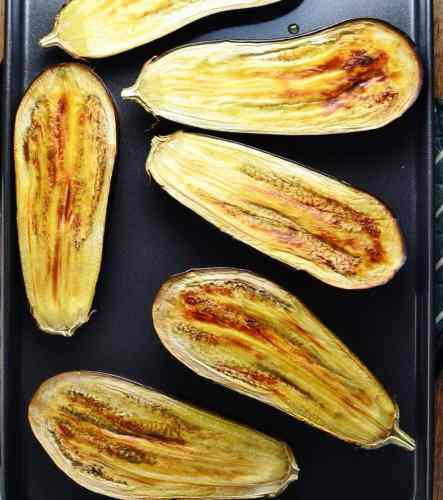 Roasted eggplant halves on oven tray.