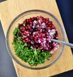 Chopped onions, pomegranate seeds and cilantro in see through bowl with spoon on wooden board.