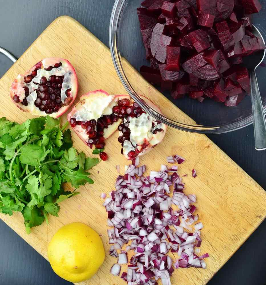 Cut pomegranate, lemon, chopped cilantro and onion on wooden board with bowl of cubed beets.