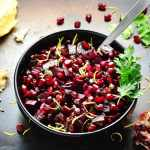 Beetroot salsa with pomegranate in black bowl with spoon and lemon, cilantro and pomegranate seeds scattered on dark brown surface.