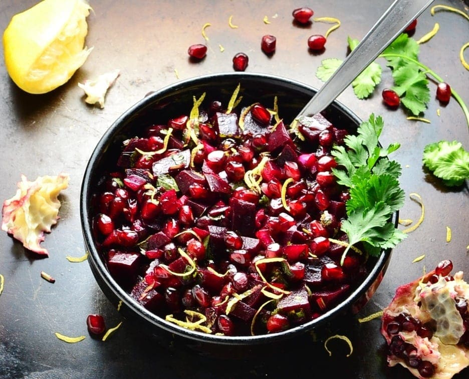 Pomegranate beetroot salad with spoon in black bowl, cilantro and lemon on dark brown surface.