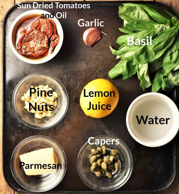 Ingredients for making sun dried tomato pesto in individual dishes.