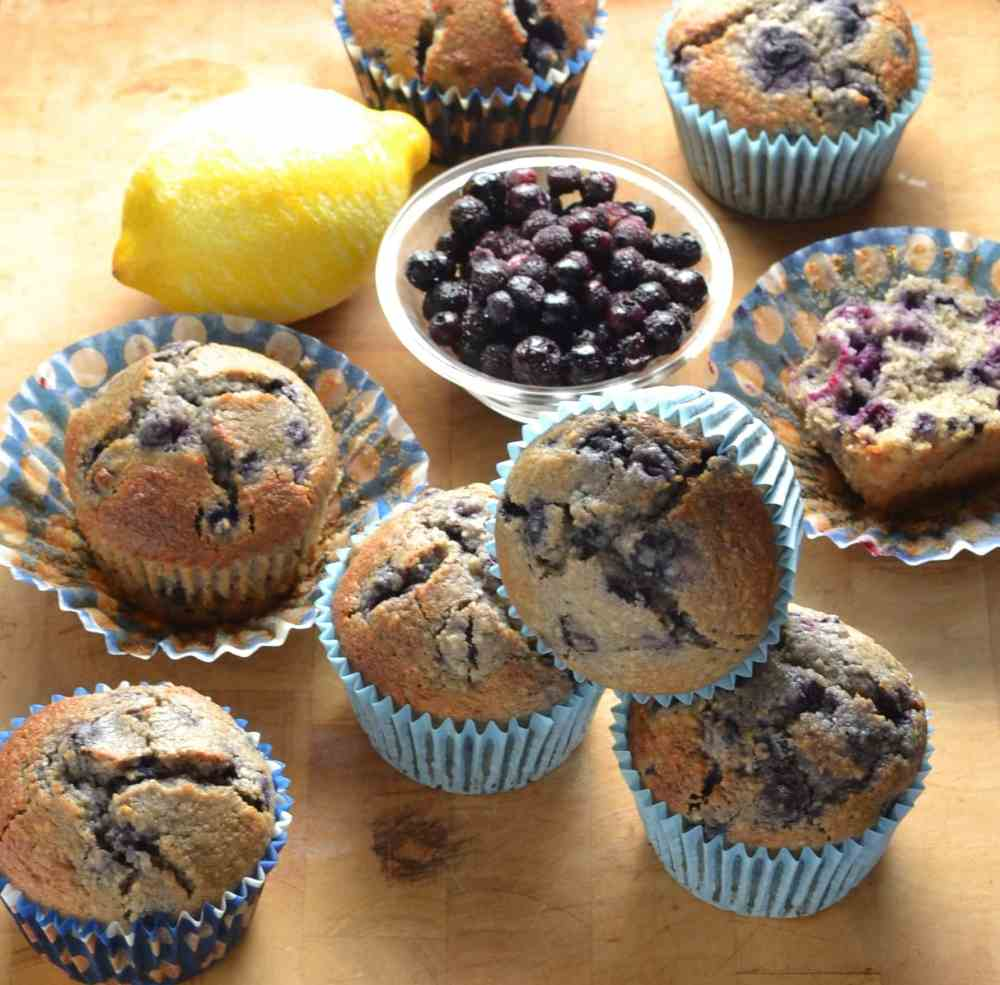 Blueberry muffins in blue paper cases with lemon and blueberries in small dish on top of wooden table.