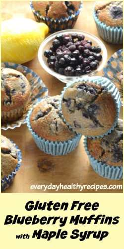 Close-up view of blueberry muffins in blue paper cases with blueberries in small dish and lemon in background on top of wooden table.
