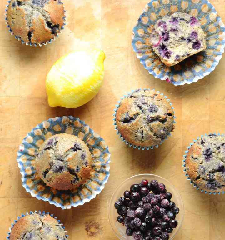 Blueberry muffins with maple syrup in blue paper cases with lemon and small dish with blueberries on wooden surface.