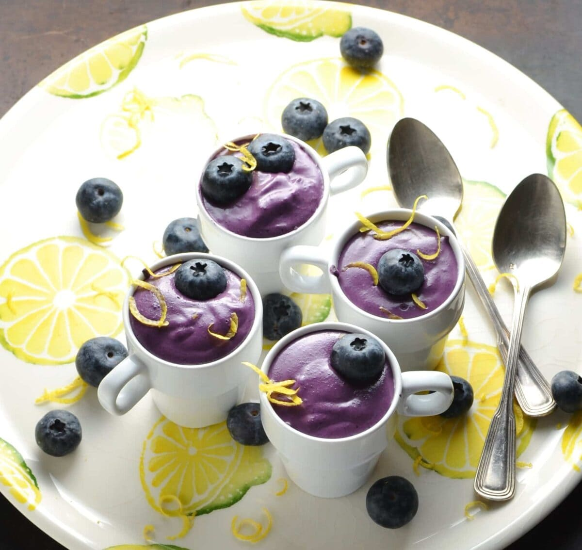 Blueberry cream cheese dessert in 4 white cups with garnish of blueberries and lemon zest, with 2 spoons on white plate with lemon pattern.