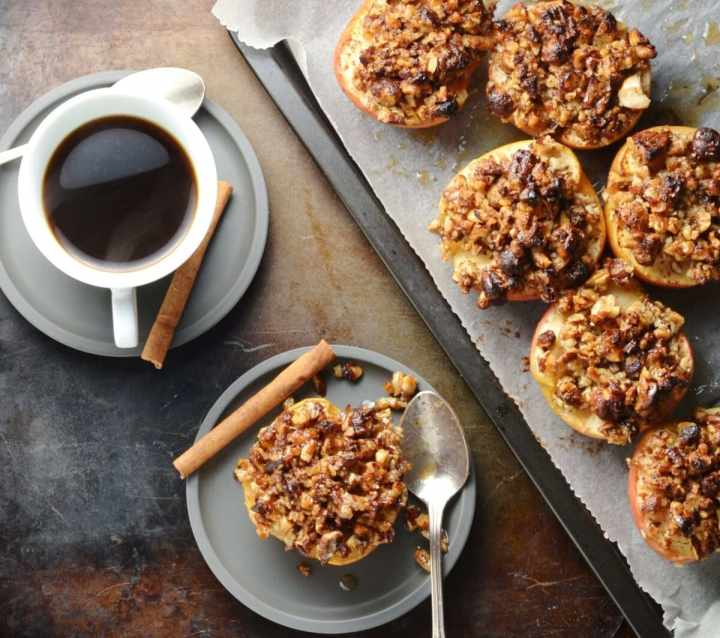 Top down view of apple halves with browned pecans on top of baking sheet and grey saucer, with coffee in white cup and grey saucer.