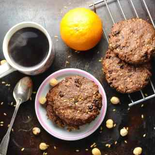 Chocolate oatmeal cookies on small plate and cooling rack, with spoon, orange, hazelnuts and cup of steaming coffee on dark brown surface