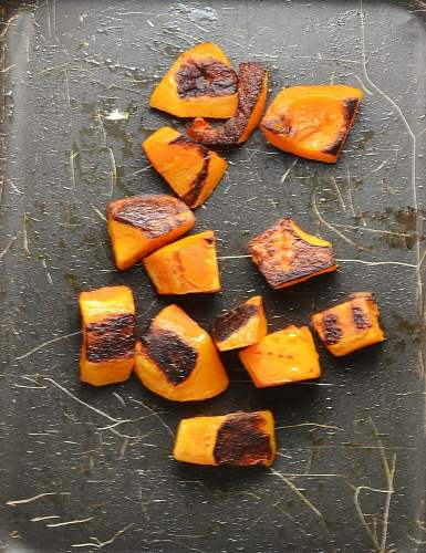 Roasted cubes of butternut squash on top of baking sheet.