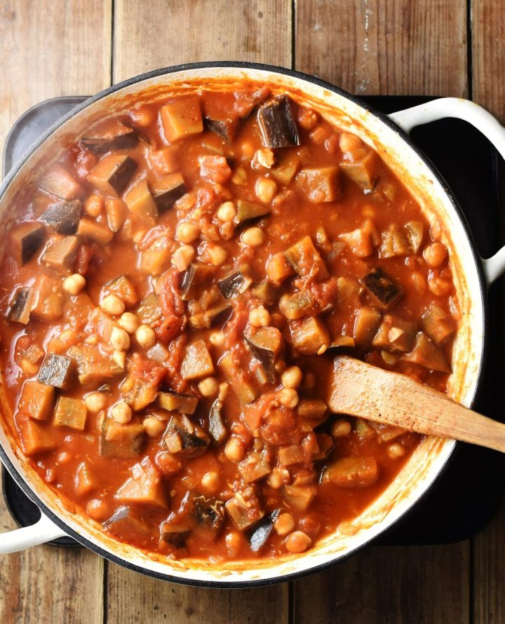 Eggplant in tomato sauce in large shallow white pan with wooden spatula.