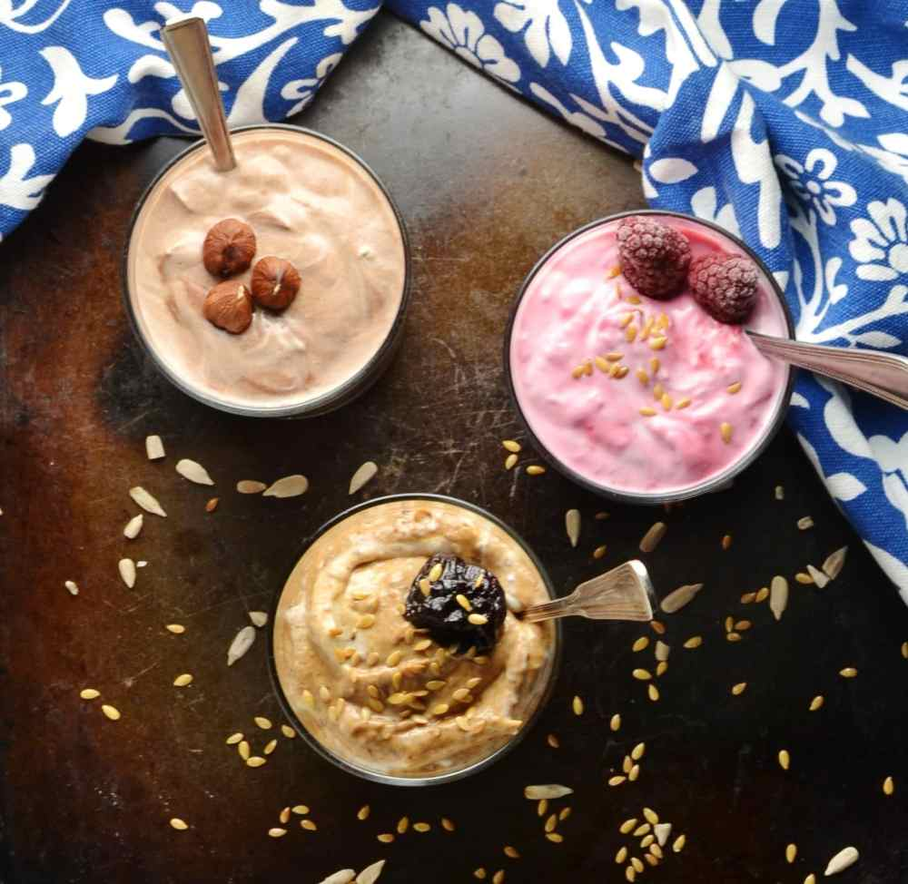 Flavoured mocha, raspberry and prune yogurt in bowls with spoons and blue-and-white cloth on brown surface.