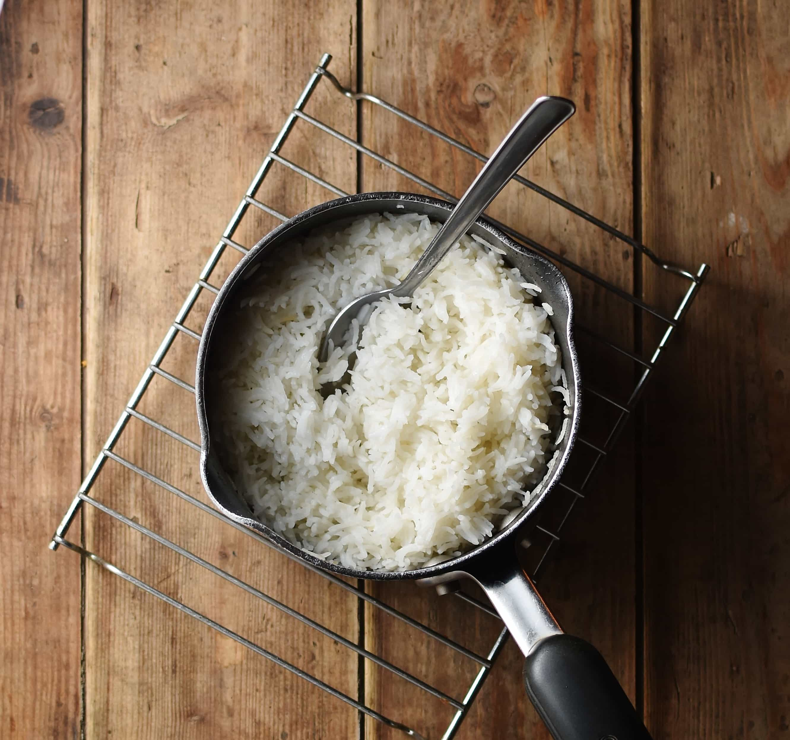 Cooked rice in saucepan with spoon on top of cooling rack.