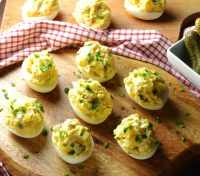 Potato salad deviled eggs with garnish of chives on wooden board with red-and-white checkered cloth in background.