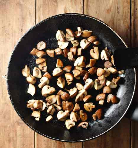 Chopped mushrooms in large frying pan with black spatula to the right.