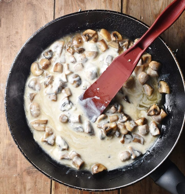 Chopped mushrooms in creamy sauce inside large pan with red spatula.