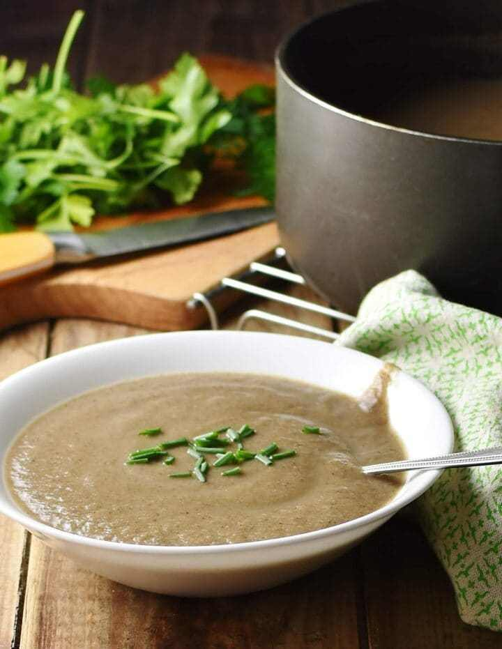 Creamy mushroom soup with chives in white bowl with spoon, green cloth, herbs, knife and large pot in background.