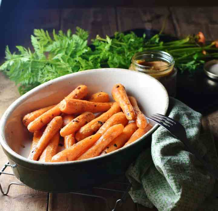 Roasted glazed carrots in oval dish with fork, green cloth to the right, miso paste in open jar and herbs in background.