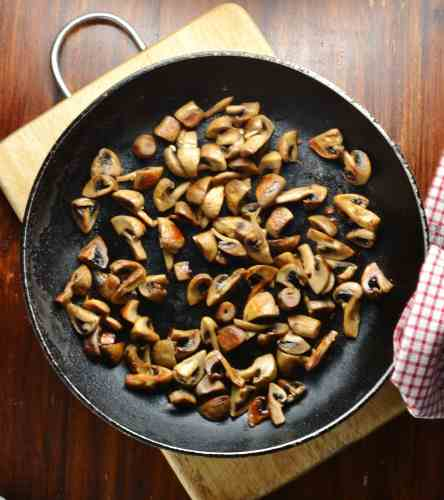 Top down view of fried mushrooms in skillet on top of wooden board.