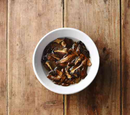Dried porcini mushrooms in small white bowl with water.