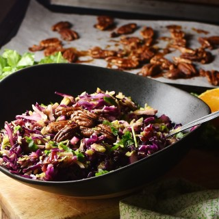 Red cabbage Christmas slaw with pecans and herbs in black bowl with spoon, and pecans on top of baking sheet with parchment paper in background.