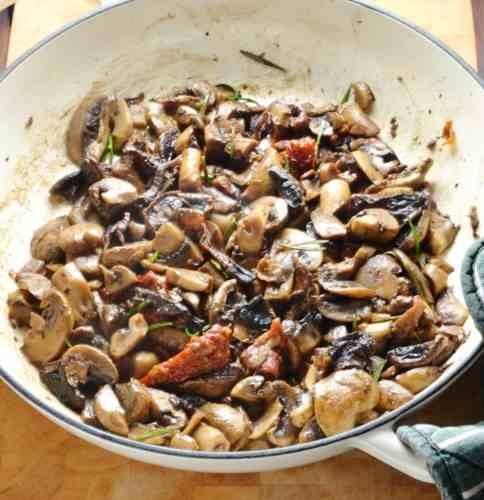 Fried mushrooms in white casserole dish on wooden board.