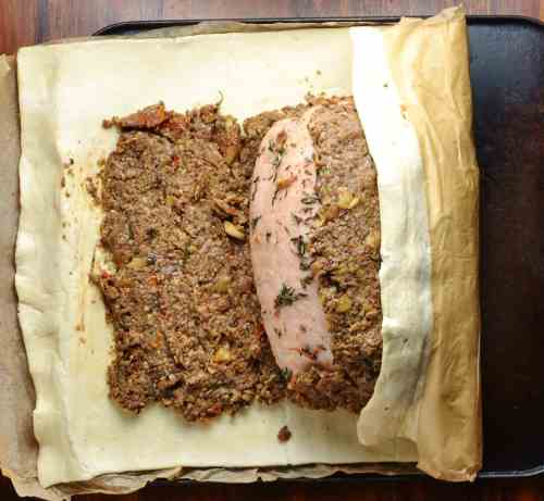 Wrapping turkey wellington in pastry with baking paper on oven tray.