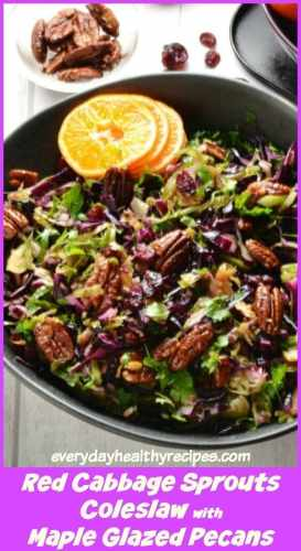 Top down view of Christmas slaw with orange slices in black bowl with pecans in background.