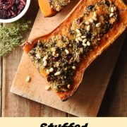 Stuffed squash on top of wooden board, with cranberries in white dish to the left.