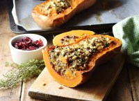 Side view of stuffed butternut squash half on wooden board, with squash, dried cranberries and thyme in background.