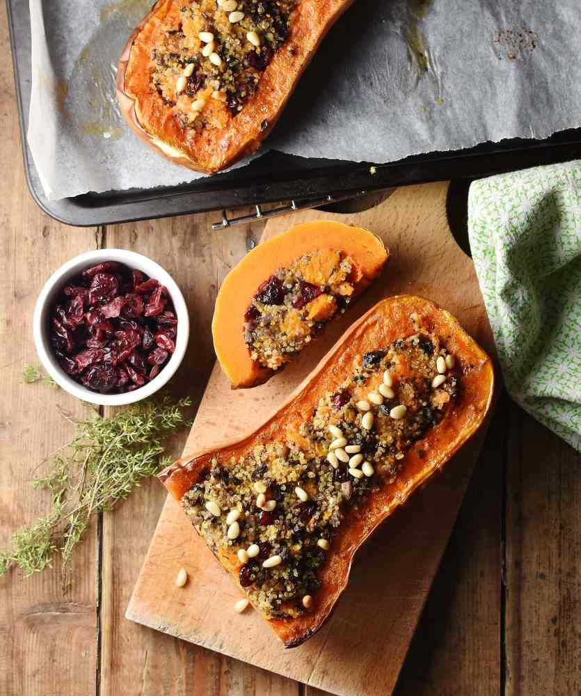Stuffed butternut squash halve with slice on top of wooden board, with green cloth, more squash, thyme and dried cranberries in dish in background.