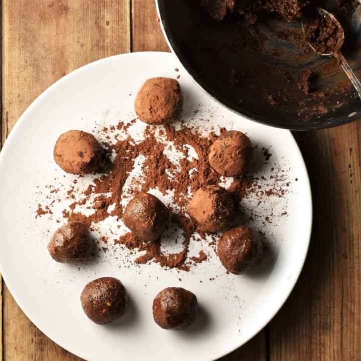 Chocolate balls on top of white plate with cocoa powder and bowl in top right corner.