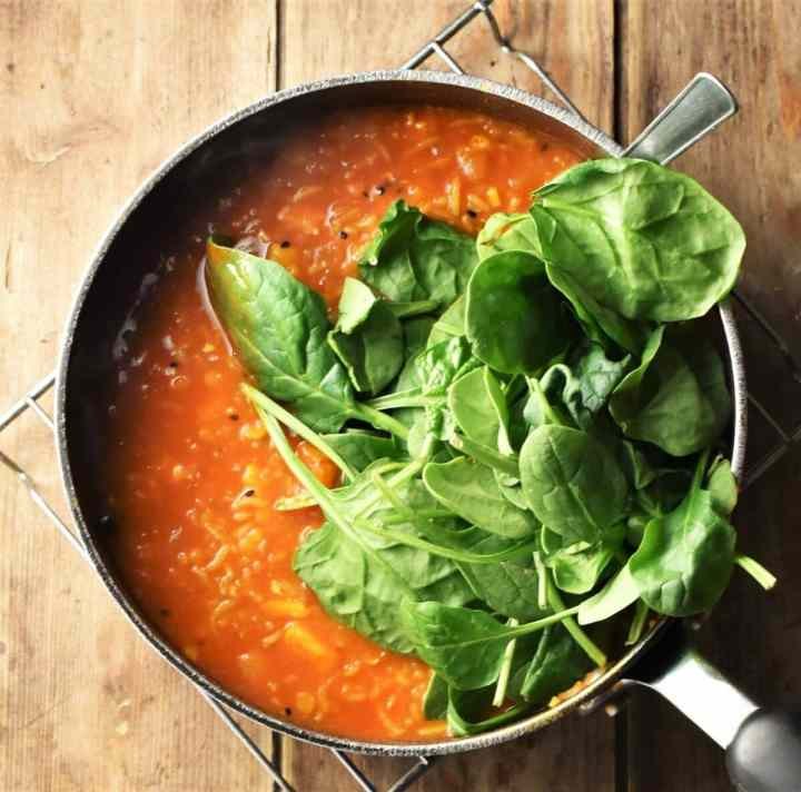 Mulligatawny rice soup with spinach in large pot.