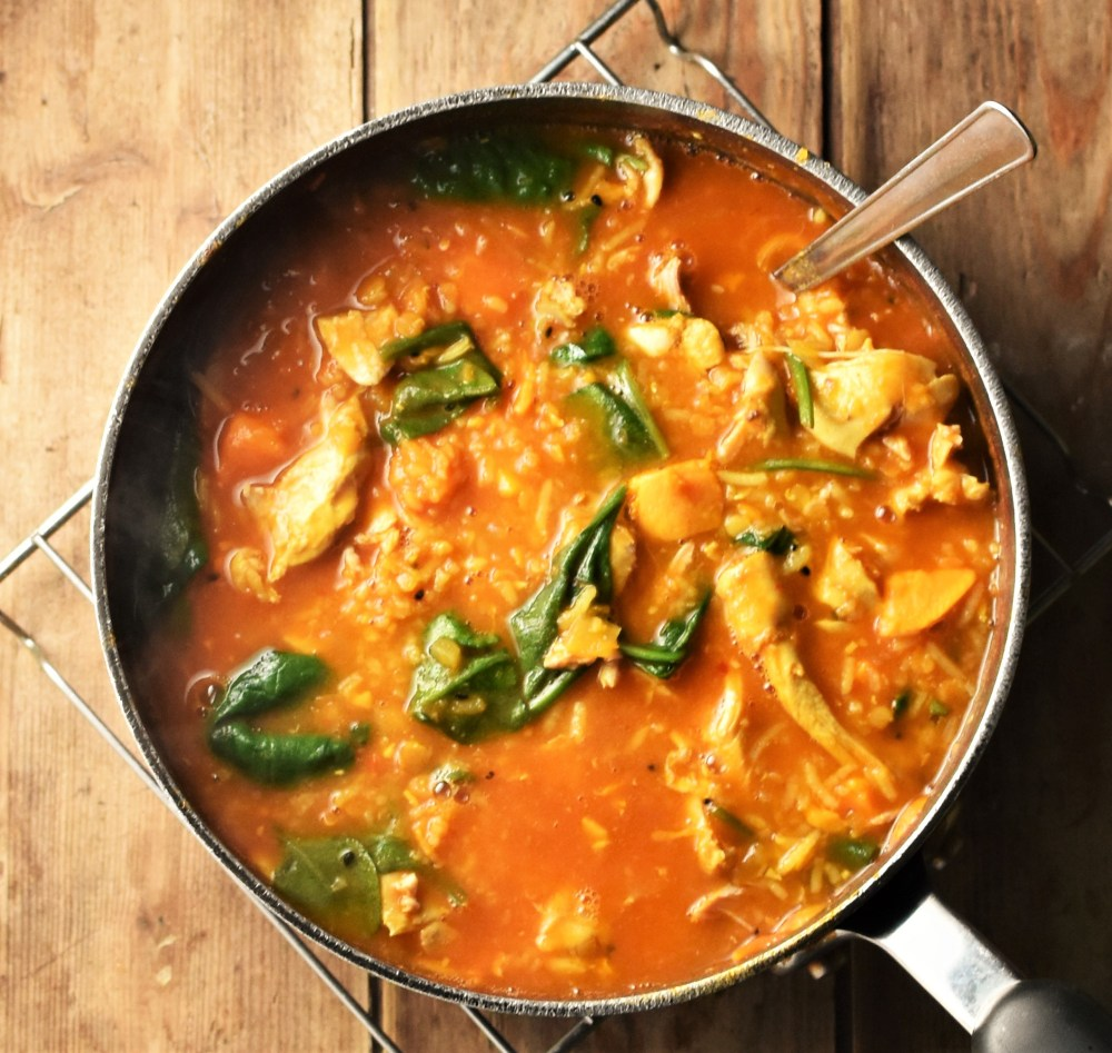 Chicken mulligatawny soup with spinach and sweet potato in large pot with spoon.