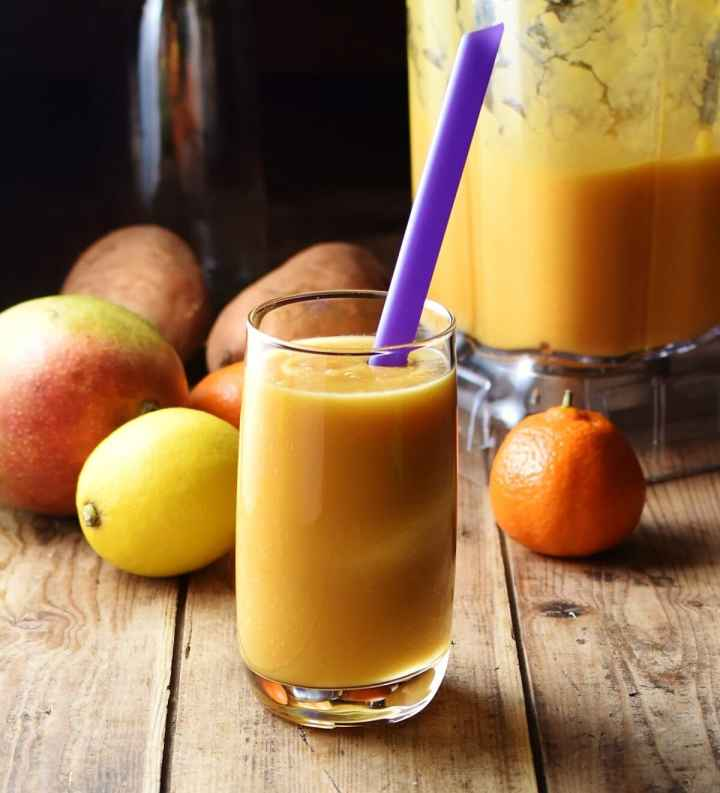 Sweet potato yellow smoothie in glass with purple straw, with tangerine, lemon, mango, sweet potatoes and smoothie in blender in background.