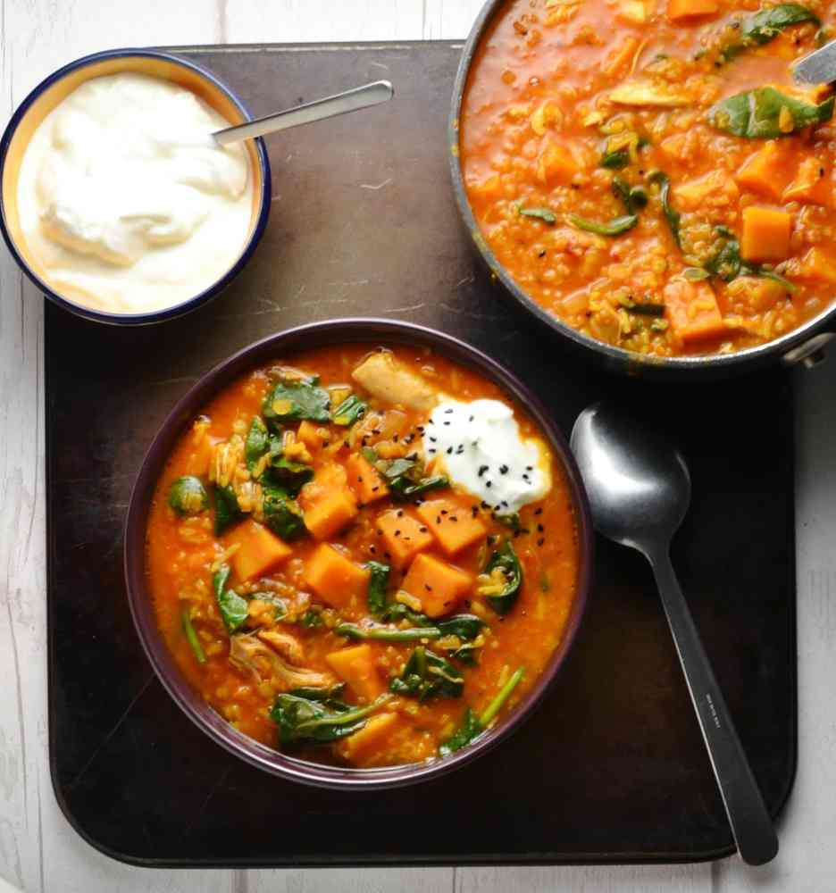 Top down view of chicken mulligatawny soup in bowl and saucepan with small bowl of yogurt with spoon on oven tray.