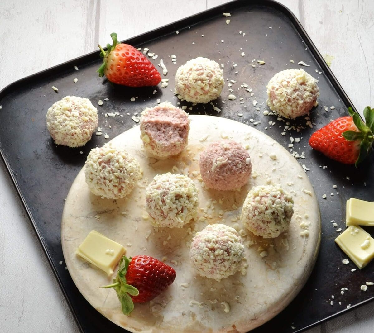 Strawberry cheesecake balls on round marble plate with strawberries and white chocolate on oven tray.