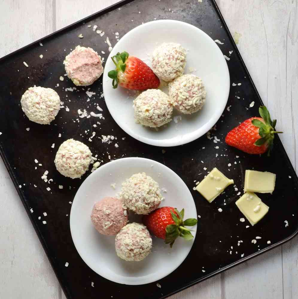 Strawberry cheesecake bites on two small white plates with white chocolate and strawberries on dark oven tray.