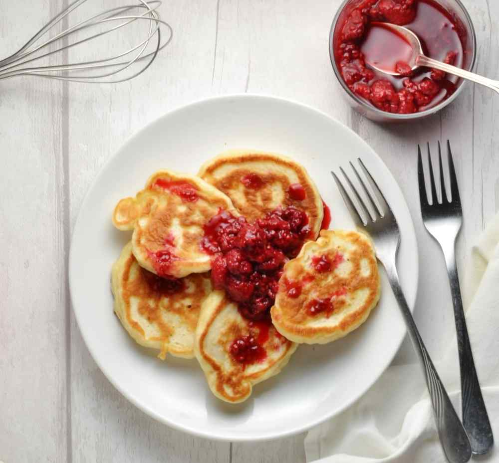 Polish pancakes with a dollop of raspberry compote on white plate with forks and raspberry compote in round dish and whisk in background.