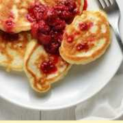 Top down view of pancakes with fruit compote and fork on top of white plate.
