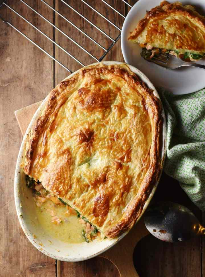Salmon pie with golden brown pastry in white oval dish, green cloth to the right and pie in white bowl in top right corner.