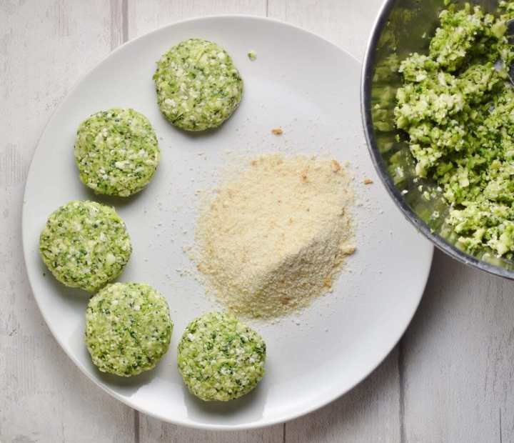 Top down view of raw broccoli patties with breadcrumbs on white plate.