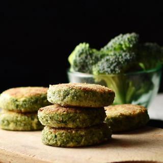 Side view of broccoli patties stacked on wooden board with broccoli florets in small dish in background.