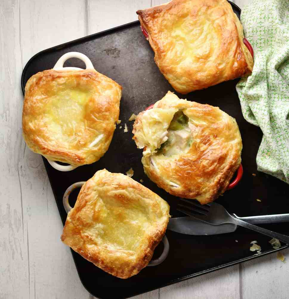 Top down view of mini chicken pot pies with knife, fork and green cloth to right on top of dark tray.