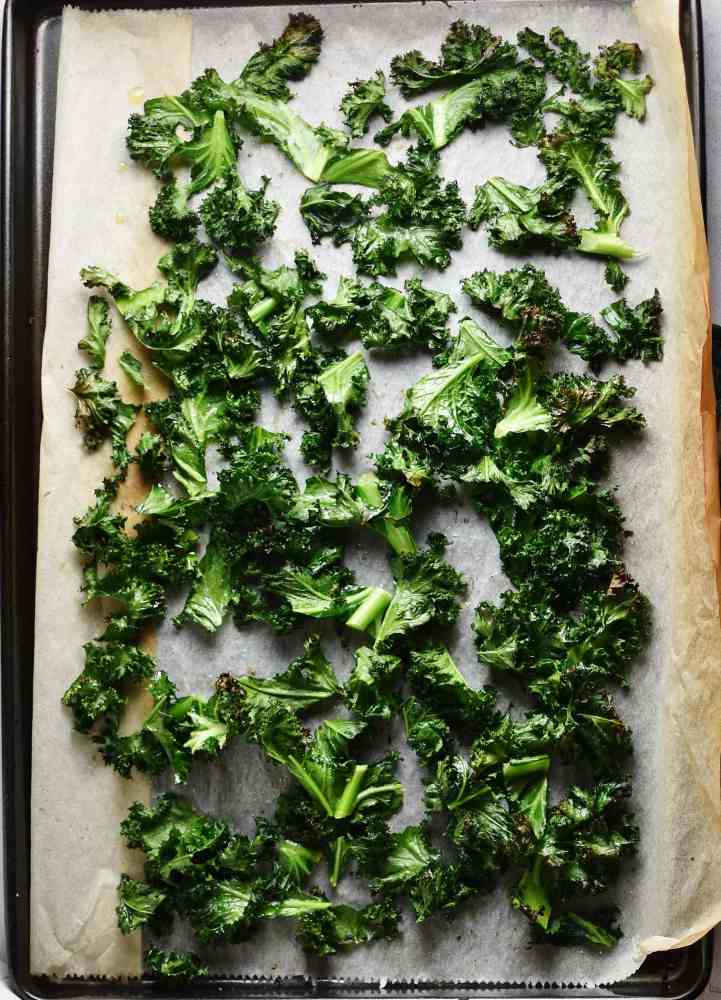 Top down view of crispy kale leaves on top of parchment paper.