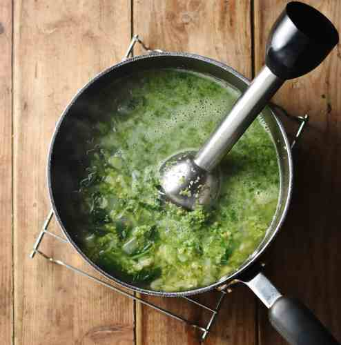 Partly pureed broccoli soup with stick blender in large pot.